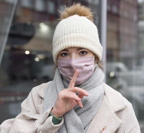 戴着医用口罩的女人在城里要求安静