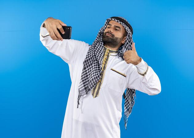 身着传统服装的阿拉伯男子用智能手机自拍 站在蓝色墙壁上竖起大拇指