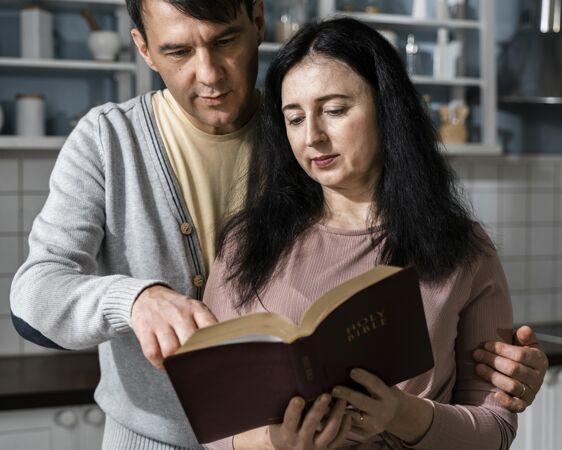 男人和女人在厨房阅读圣经的正面图