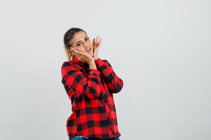 年轻女子枕在她的手上的脸在格子衬衫和看起来可爱 前视图